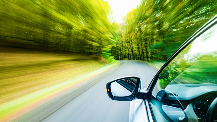 Car driving on road surrounded by forest
