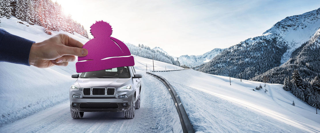 SUV driving on snowy road while a hand reaches out to put a purple stocking cap on it
